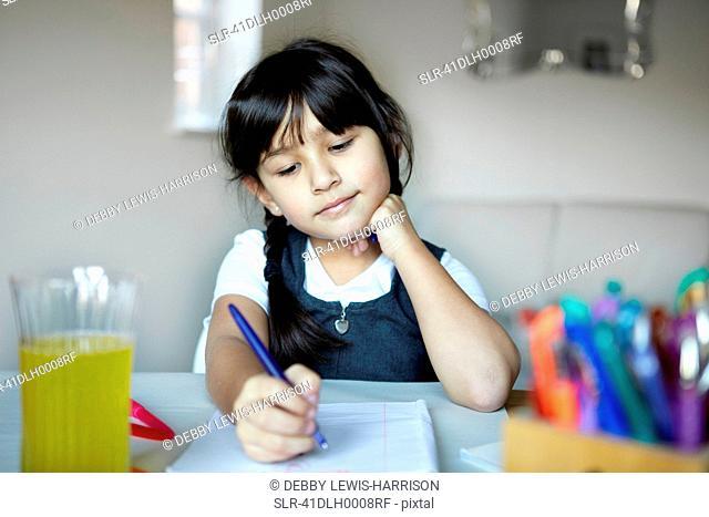 Schoolgirl writing at desk