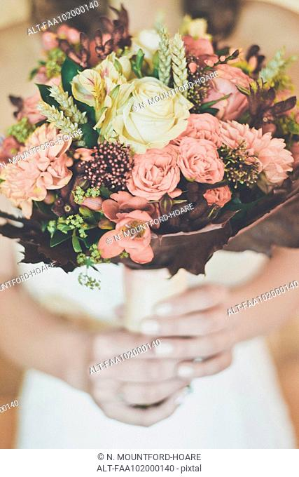 Bride holding bouquet, cropped