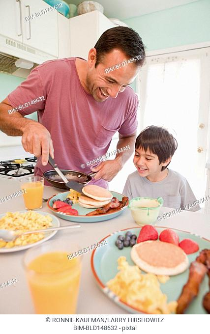 Hispanic father making breakfast for son