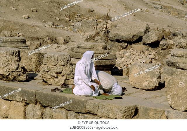 Two muslim men pray towrds Mecca