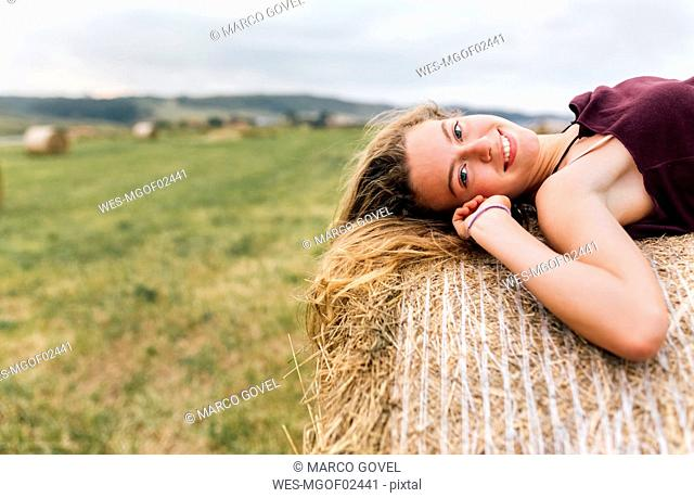 Portrait of smiling blond teenage girl lying on straw bale