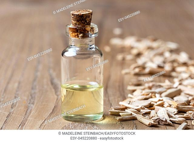 A bottle of essential oil with cedar wood chips on a table