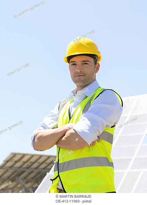 Worker standing by solar panels in rural landscape