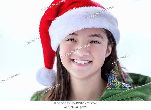 A young teen girls dons a santa hat and a big smile