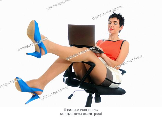 Short hair business woman on a laptop sitting in an office chair with blue heels