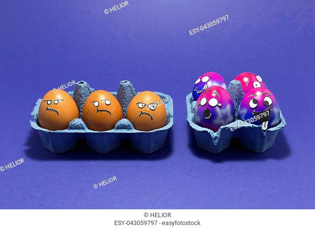 Group of colorful painted Easter eggs with funny cartoon style faces and group of grumpy looking brown eggs in light blue egg boxes on purple background