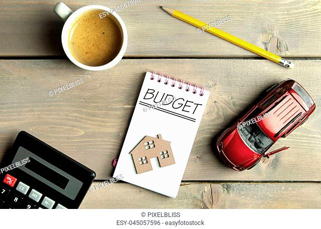 Budget handwritten in a notepad with a miniature car and house