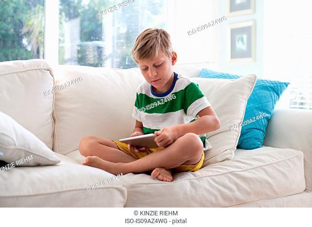 Boy sitting on sofa using digital tablet