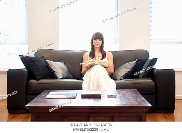 Caucasian woman reading book on living room sofa