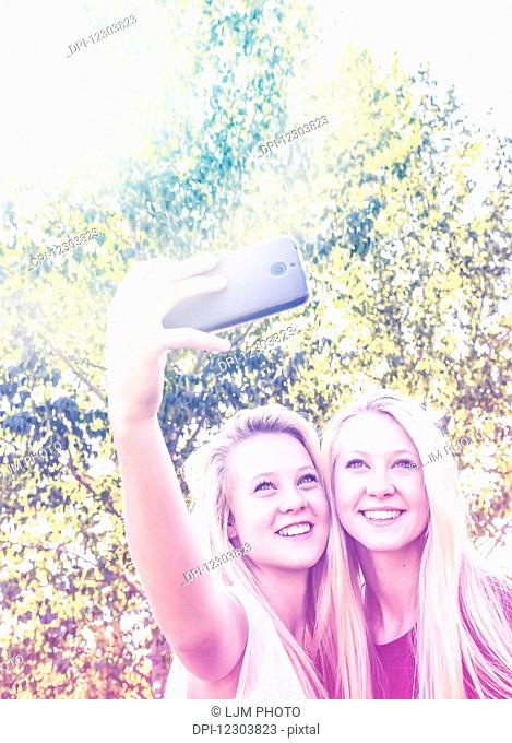 Two sisters having fun outdoors in a city park in autumn and taking selfies of themselves; Edmonton, Alberta, Canada