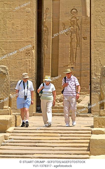 Goddess Isis in relief carving in the background as Tourist's visit Philae Temple, Aswan, Egypt, North Africa