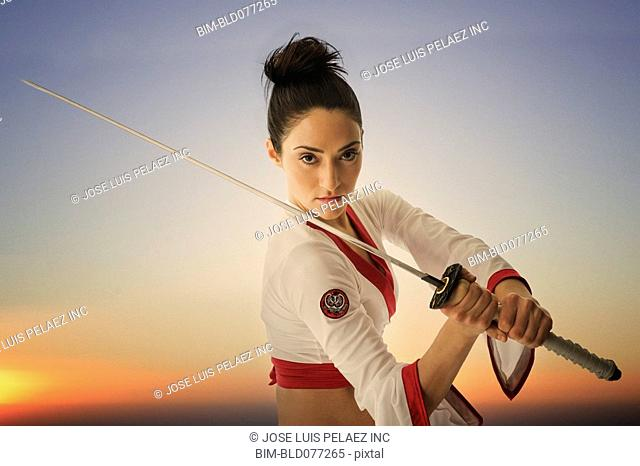 Mixed race woman performing martial arts with sword