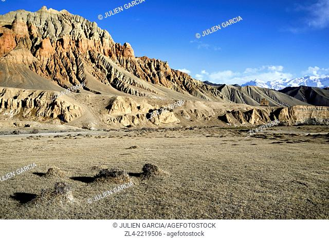 Red and ochre rock formations in a valley near Dhakmar village. Nepal, Gandaki, Upper Mustang (near the border with Tibet)