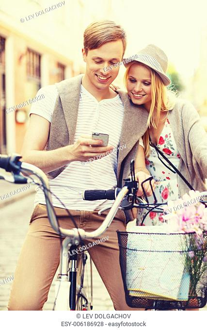 summer holidays, love, navigation, gps and dating concept - couple with bicycles and smartphone in the city