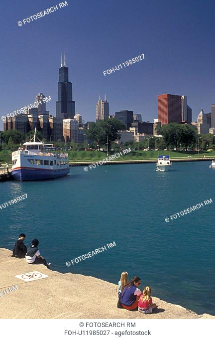 Chicago, IL, Lake Michigan, Illinois, People watching a sightseeing tour boat in the Chicago Harbor from Grant Park with a view of the downtown skyline of...