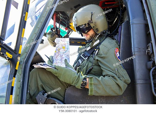 Gilze-Rijen, Netherlands. Captain and Pilot of a cougair airforce helicopter preparing his flight, previous from take off from a military airfield