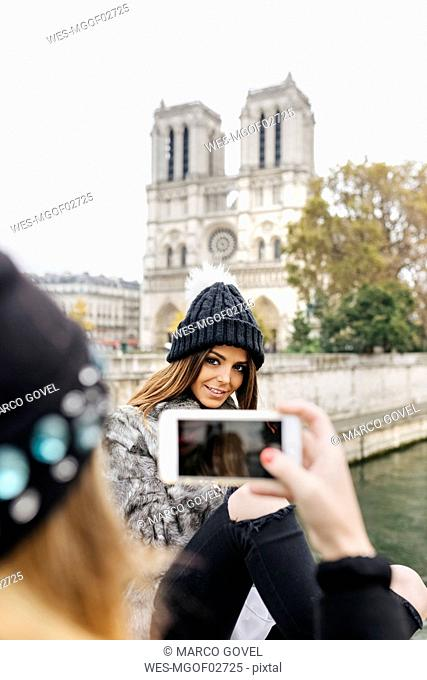 France, Paris, tourist taking picture of her friend in front of Notre Dame