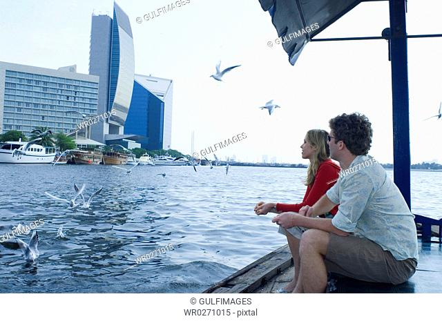 Couple feeding sea gulls on Abra at Dubai Creek, United Arab Emirates
