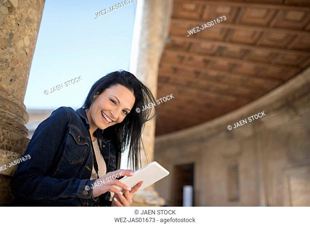 Spain, Granada, happy young woman with tablet at the Alhambra