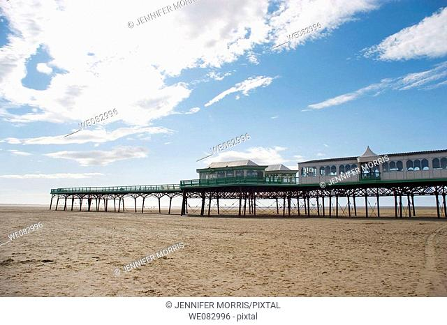 The pier at St Anne's in Lancashire, stretching out over the brown sand beach. The tide is out and white puffy clouds streak the blue sky