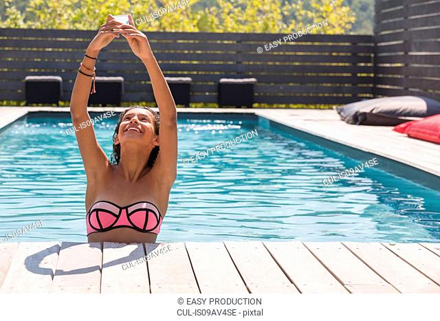 Girl holding up smartphone for selfie in swimming pool, Cassis, Provence, France