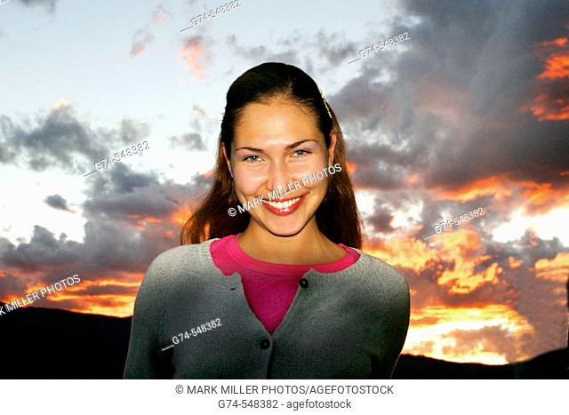 A young woman smiles in the colors of sunset