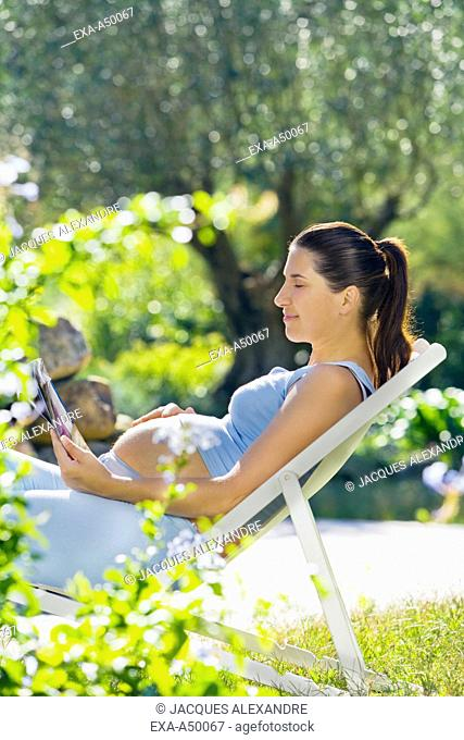 Young pregnant woman reading a magazine in the garden on a bright sunny day