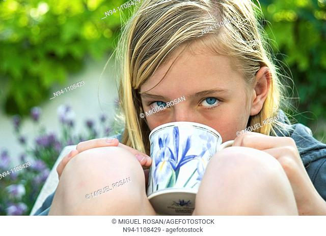 Close up of teenage girl with a cup of soup in the garden