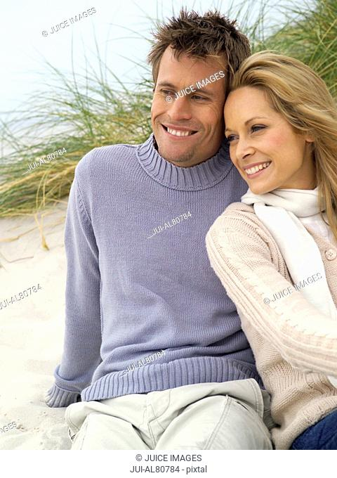 Couple hugging in dunes on beach