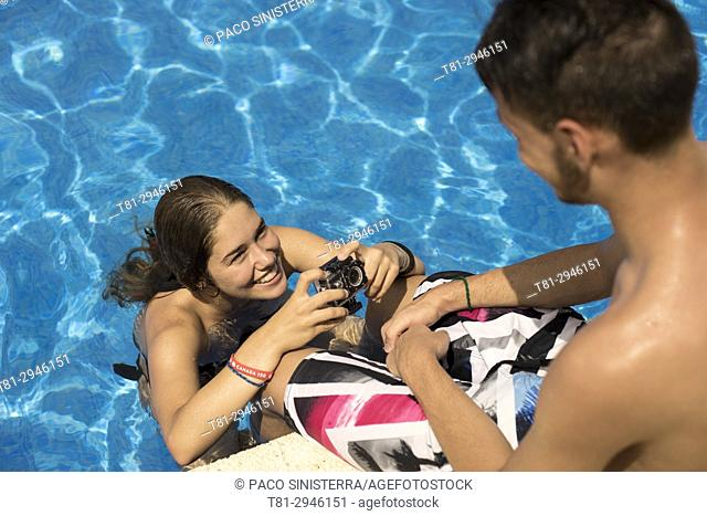teenagers taking photos in the pool.Peñiscola, Castellon, Spain
