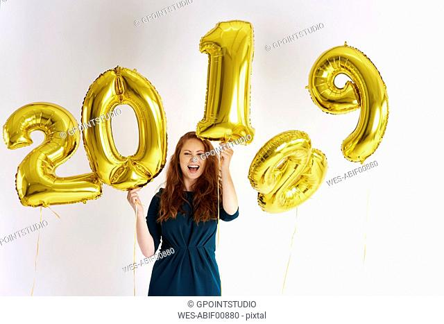 Portrait of happy young woman with golden balloons forming the date '2019'