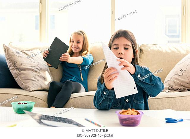 Girls at home using digital tablet, making paper airplane
