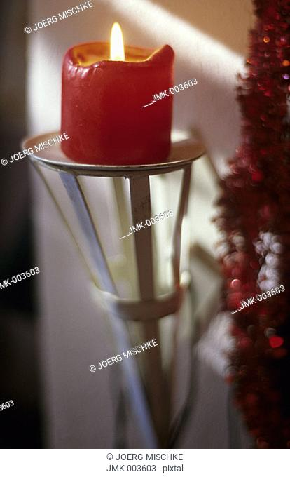 A burning candle on a candlestick