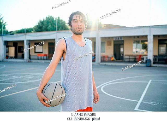 Portrait of man on basketball court holding basketball looking at camera
