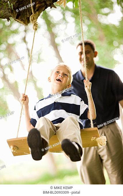 Caucasian father pushing son on swing