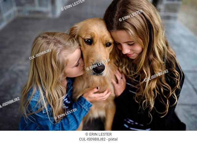 Girl and her sister sitting on patio petting their golden retriever