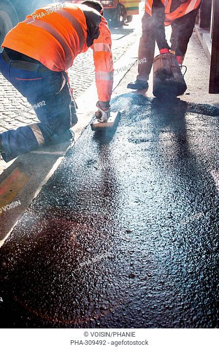 Workmen resurfacing a section of a sidewalk
