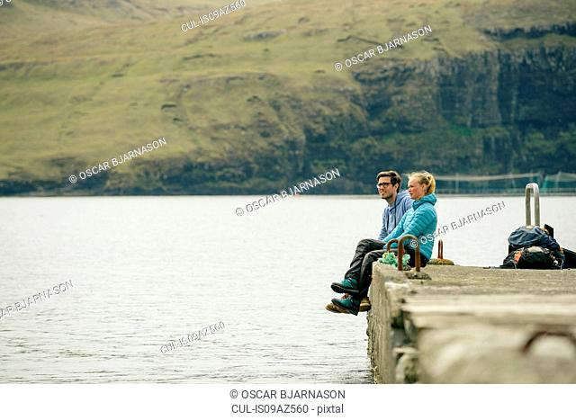 Hikers on pier, Vagar, Faroe Islands