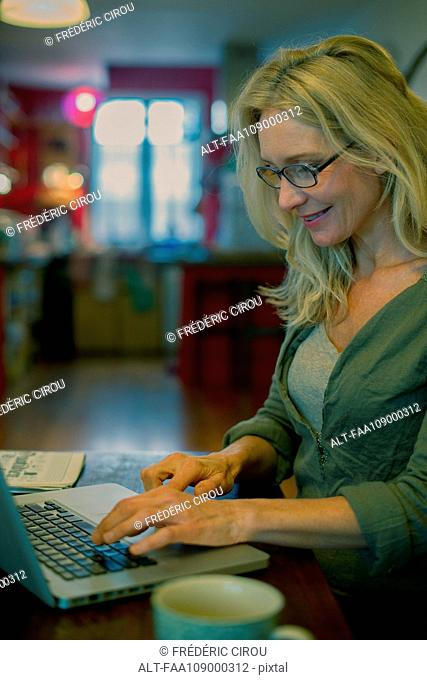 Mature woman using laptop computer at home