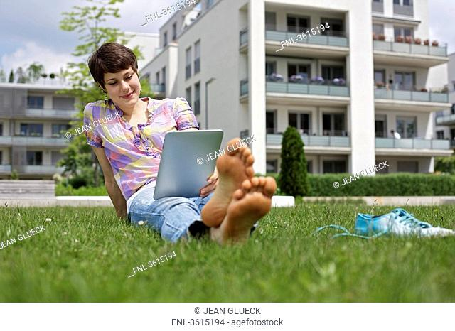 Young woman using iPad in grass