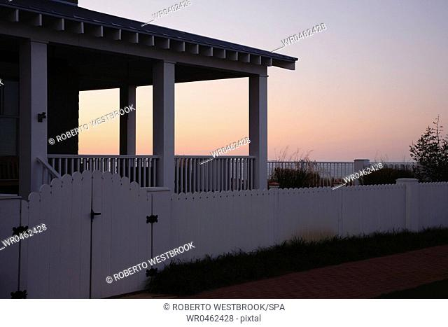 Covered Porch And Fence At Sunset
