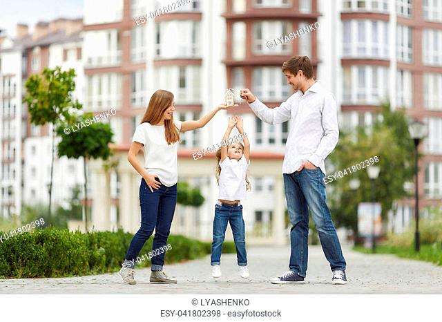 Adorable little girl reaching to the keys her parents are holding. Family posing outdoors in front of a modern apartment building