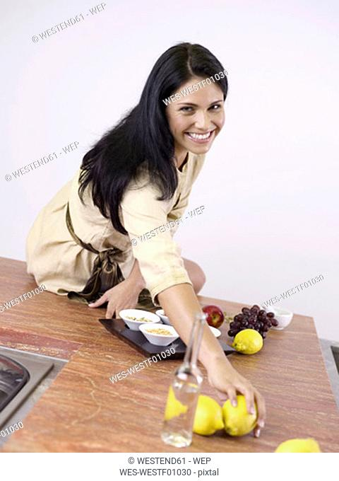 Woman in kitchen with fruits, smiling, portrait