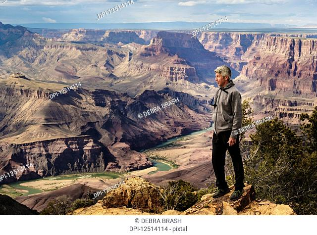 A senior man hiking in the Grand Canyon and standing on a ridge looking out over the landscape; Arizona, United States of America