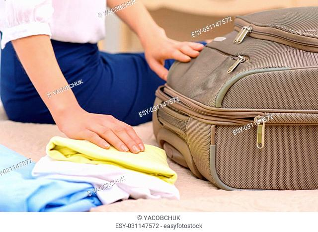Unpacking time. Young nice-looking female tourist opens suitcase and starts unpacking