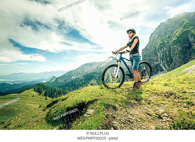 Germany, Bavaria, Pfronten, woman with mountain bike on alpine meadow near Aggenstein