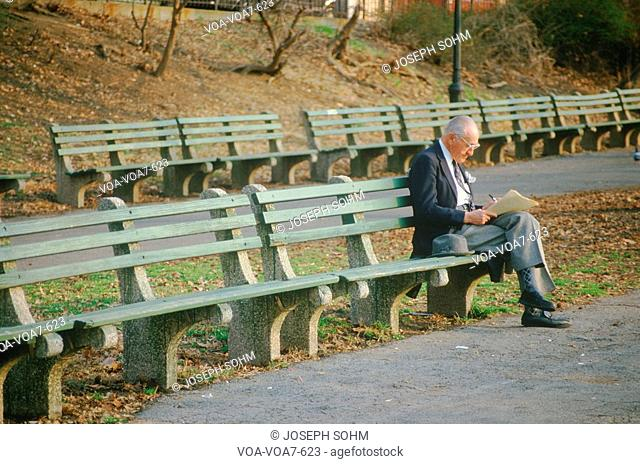 A well dressed senior reading on a park bench, NY City