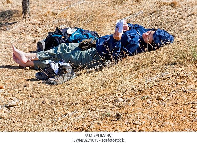 female pilgrim having a break at the border of the Way of St James, Spain, Kastilien und Len, Palencia, Calzadilla de la Cueza