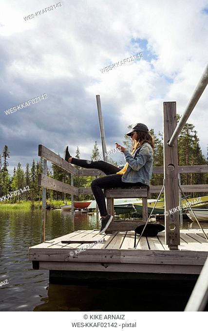 Finland, Lapland, woman sitting on jetty at a lake using cell phone