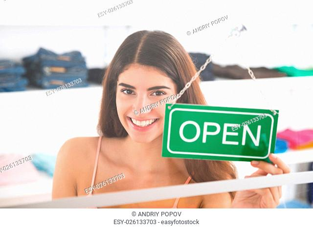 Portrait of smiling female owner holding open sign in clothing store